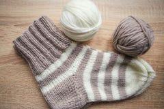 Il filato beige e bianco, Knitted ha barrato il calzino beige-beige è sulla tavola immagini stock