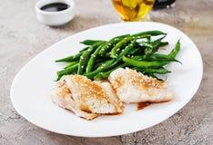 Il filetto di pesce è servito con la salsa ed i fagiolini di soia in piatto bianco immagini stock libere da diritti