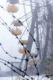 il filo spinato del metallo davanti all'attrazione della ruota di ferris nell'inverno nebbioso ha abbandonato il parco di diverti fotografia stock