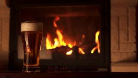 Il filtraggio ha sparato il vetro pieno della birra raffreddata appetitosa del rinfresco con schiuma circondata dal camino video d archivio