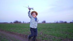 Il fine settimana felice, bambino tiene l'aereo del giocattolo e funziona lungo il campo verde video d archivio
