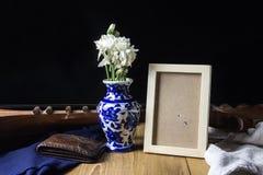Il fiore bianco in portafoglio blu del cuoio del vaso e la foto incorniciano la l tranquilla Immagini Stock