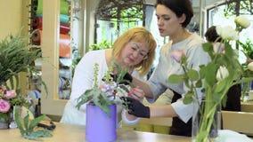 Il fiorista con l'assistente crea la composizione nel fiore archivi video