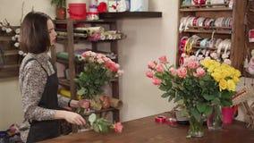 Il fiorista sveglio dell'apprendista raccoglie un mazzo delle rose in un negozio di fiore video d archivio