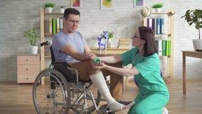 Il fisioterapista aiuta una persona in una sedia a rotelle dopo una lesione a fare gli esercizi con l'estensore del polso stock footage