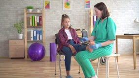 Il fisioterapista dice un adolescente con i problemi ortopedici circa i sottopiedi ortopedici per la correzione del piede valgo video d archivio