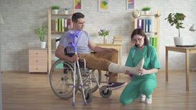 Il fisioterapista esamina la gamba rotta di un uomo in una sedia a rotelle dopo una lesione video d archivio