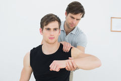 Il fisioterapista maschio che esamina giovane il braccio fotografia stock