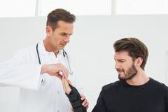 Il fisioterapista maschio che esamina giovane il polso dentro fotografia stock libera da diritti