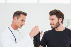Il fisioterapista maschio che esamina la a equipaggia il polso fotografia stock