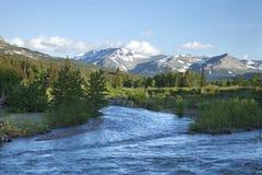 Il fiume e le montagne si avvicinano al Glacier National Park alla luce di mattina Fotografia Stock