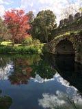 Il fiume ed il ponte di pietra nel giardino di Ninfa, Italia Immagini Stock
