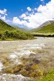 Il fiume entra in montagna contro cielo blu 2 Immagini Stock