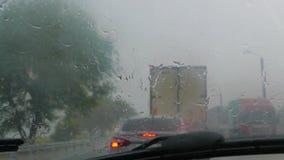 Il flusso delle macchine sta muovendosi lungo la strada nella pioggia archivi video