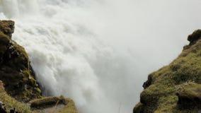 Il flusso rapido della cascata potente fra due rocce ha coperto il muschio, vista epica stock footage