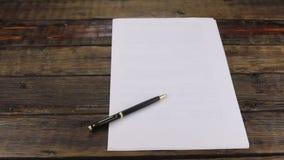 Il foglio bianco di carta e della maniglia nera della scrofa giovane si trova sulla scrivania di legno d'annata colpo del cursore stock footage