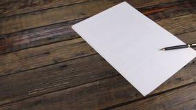 Il foglio bianco di carta e della maniglia nera della scrofa giovane si trova sulla scrivania di legno d'annata colpo del cursore video d archivio