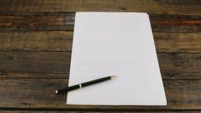 Il foglio bianco di carta e della maniglia nera della scrofa giovane si trova sulla scrivania di legno d'annata Panorama stock footage
