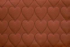 Il fondo astratto sui tessuti, tessuto del cuore ha cucito il colore di terracotta di simboli del cuore handmade fotografia stock libera da diritti