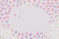 Il fondo bianco con la farfalla variopinta scintillare ha modellato i coriandoli Copi lo spazio fotografia stock