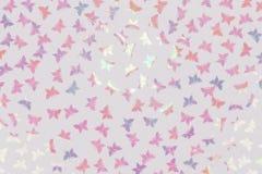Il fondo bianco con la farfalla variopinta scintillare ha modellato i coriandoli Disposizione piana fotografie stock
