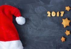 Il fondo con il cappuccio del ` s di Santa ed il pan di zenzero al forno mandano un sms a 2017 Idea creativa Fotografia Stock