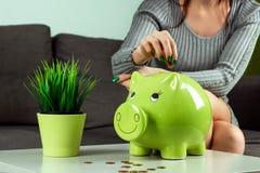 Il fondo creativo, la mano della ragazza del primo piano, getta una moneta nel porcellino salvadanaio sotto forma di maiale verde fotografia stock libera da diritti