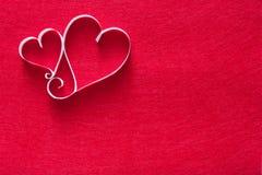 Il fondo del biglietto di S. Valentino con il cuore della carta fatta a mano modella la decorazione sul feltro di rosso Fotografia Stock