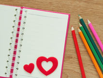 Il fondo del giorno di biglietti di S. Valentino con i cuori rossi, il libro per il diario ed il colore disegnano a matita sul pa Fotografia Stock
