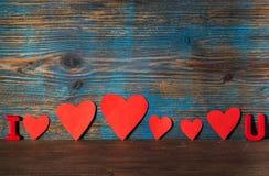 Il fondo del giorno di biglietti di S. Valentino, magnete segna la i con lettere ed u e cuori rossi Fotografia Stock