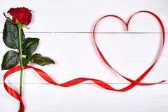 Il fondo del giorno di biglietti di S. Valentino con un rosa rossa e nastro ha modellato As Immagini Stock
