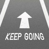 Il fondo della strada asfaltata con la freccia del segnale e la parola continuano andare royalty illustrazione gratis