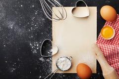 Il fondo di cottura con farina, il matterello, le uova, lo strato di carta ed il cuore modellano sulla tavola del nero della cuci fotografia stock libera da diritti