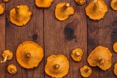 Il fondo di legno di Brown con l'arancia luminosa si espande rapidamente galletti Fotografie Stock