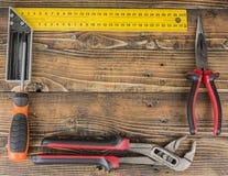 Il fondo di legno con gli strumenti gradisce il cacciavite delle pinze del righello Fotografie Stock