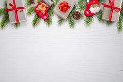 Il fondo di Natale con i regali, i calzini, i pinecones e l'abete si ramifica sulla cima Fotografie Stock Libere da Diritti