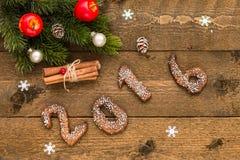 Il fondo di Natale con il pan di zenzero numera 2016, i rami dell'abete e le decorazioni sul bordo di legno anziano Immagine Stock Libera da Diritti