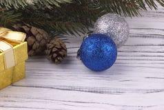 Il fondo di Natale con l'abete naturale dorato delle palle rosse e d'argento del contenitore di regalo si ramifica coni su di leg Fotografia Stock
