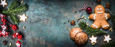 Il fondo di Natale con la decorazione, i biscotti, l'uomo di pan di zenzero e l'abete festivi si ramifica vista superiore, posto  Fotografia Stock Libera da Diritti