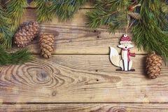 Il fondo di Natale con la volpe ed il pino decorativi si ramifica su ol Fotografia Stock