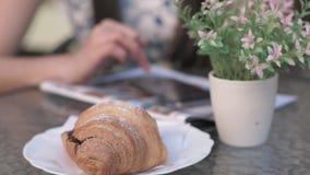 Il fondo di un croissant fiorisce gli usi della donna un telefono su uno scrittorio stock footage