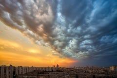 Il fondo di una tempesta del tramonto si rannuvola il paesaggio urbano Immagini Stock