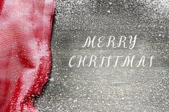 Il fondo festivo dell'inverno di festa di Natale con la tovaglia rossa luminosa ha coperto i fiocchi di neve scintillanti sulla t immagini stock libere da diritti