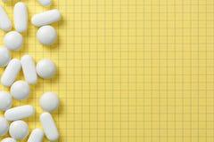 Il fondo giallo con le pillole bianche ha andato fotografie stock libere da diritti