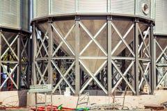 Il fondo, metallo barrels i granai sui precedenti del cielo Immagini Stock Libere da Diritti