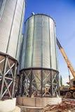 Il fondo, metallo barrels i granai sui precedenti del cielo Immagini Stock