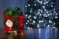 Il fondo per il messaggio di natale con rosso di Santa ha acceso l'albero di Natale del contenitore e di regalo con le luci di na immagini stock libere da diritti