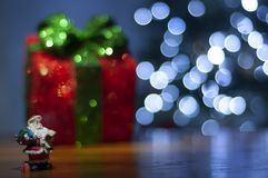 Il fondo per il messaggio di natale con rosso di Santa ha acceso l'albero di Natale del contenitore e di regalo con le luci di na fotografie stock libere da diritti
