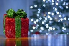 Il fondo per il messaggio di natale con rosso di Santa ha acceso l'albero di Natale del contenitore e di regalo con le luci di na fotografia stock