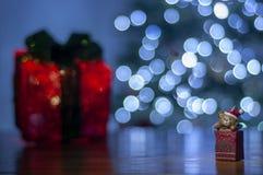 Il fondo per il messaggio di natale con rosso di Santa ha acceso l'albero di Natale del contenitore e di regalo con le luci di na fotografie stock